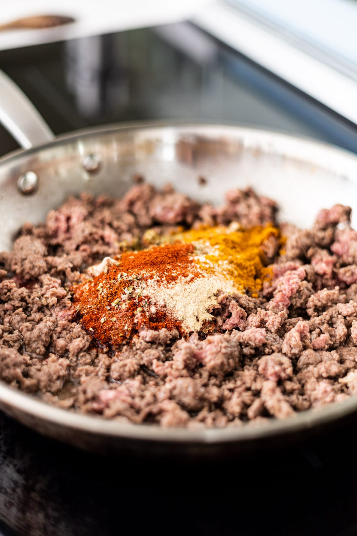 Browned beef cooking in a skillet with spices on top.