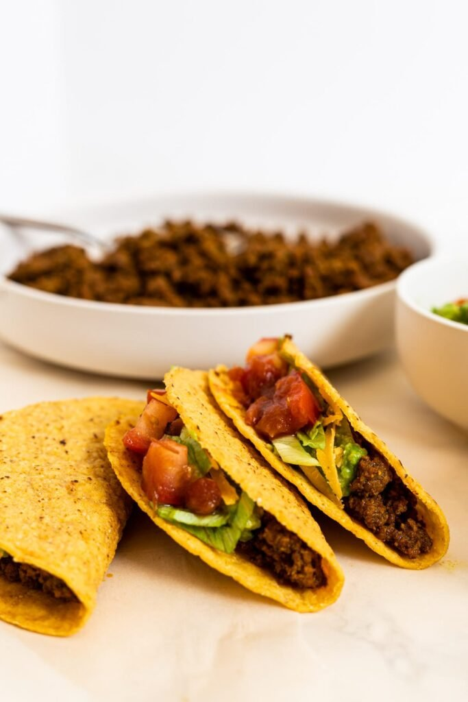 Three tacos in front of a bowl of taco meat.