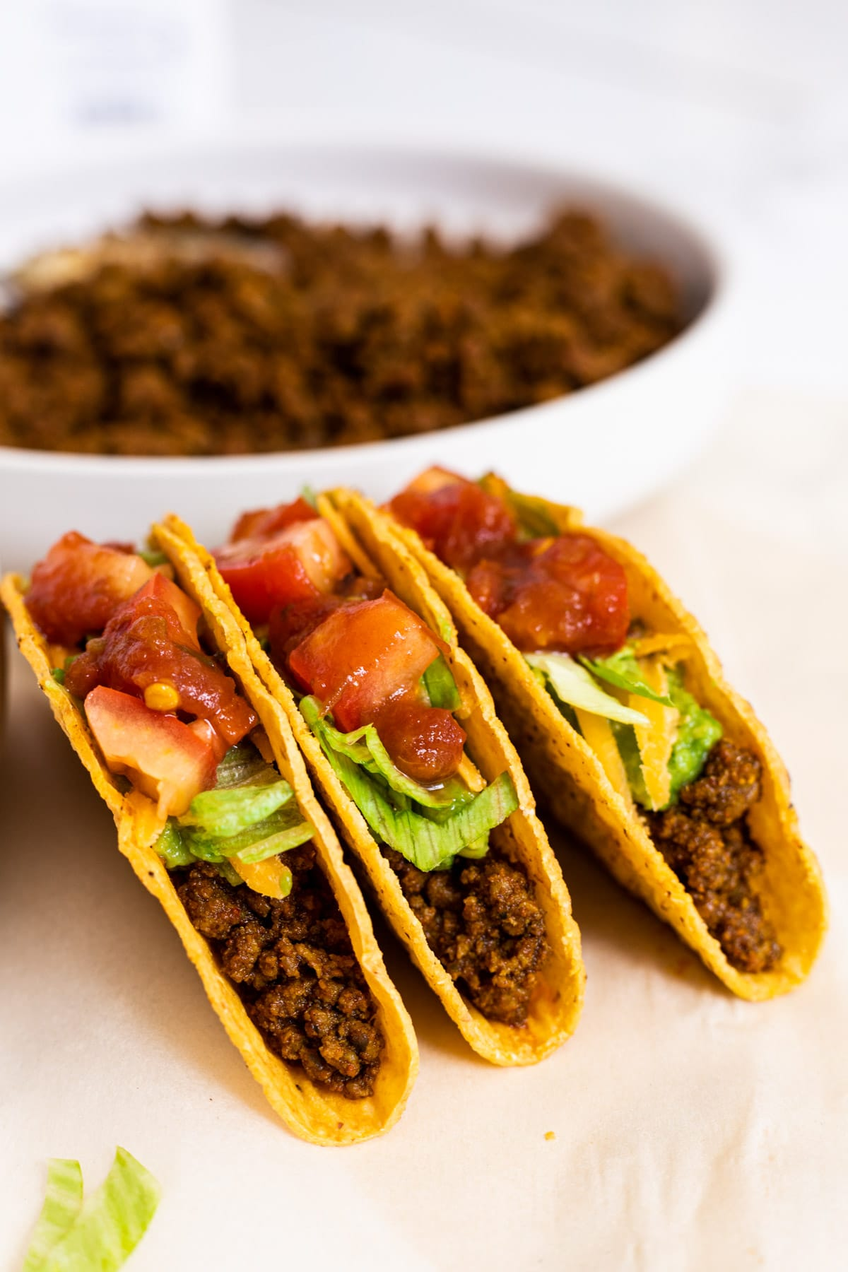 Three dressed beef tacos standing in front of a bowl of taco meat.