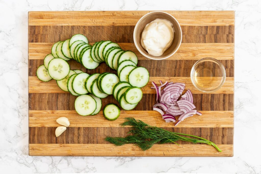 A top down view of creamy cucumber salad ingredients on a cutting board.