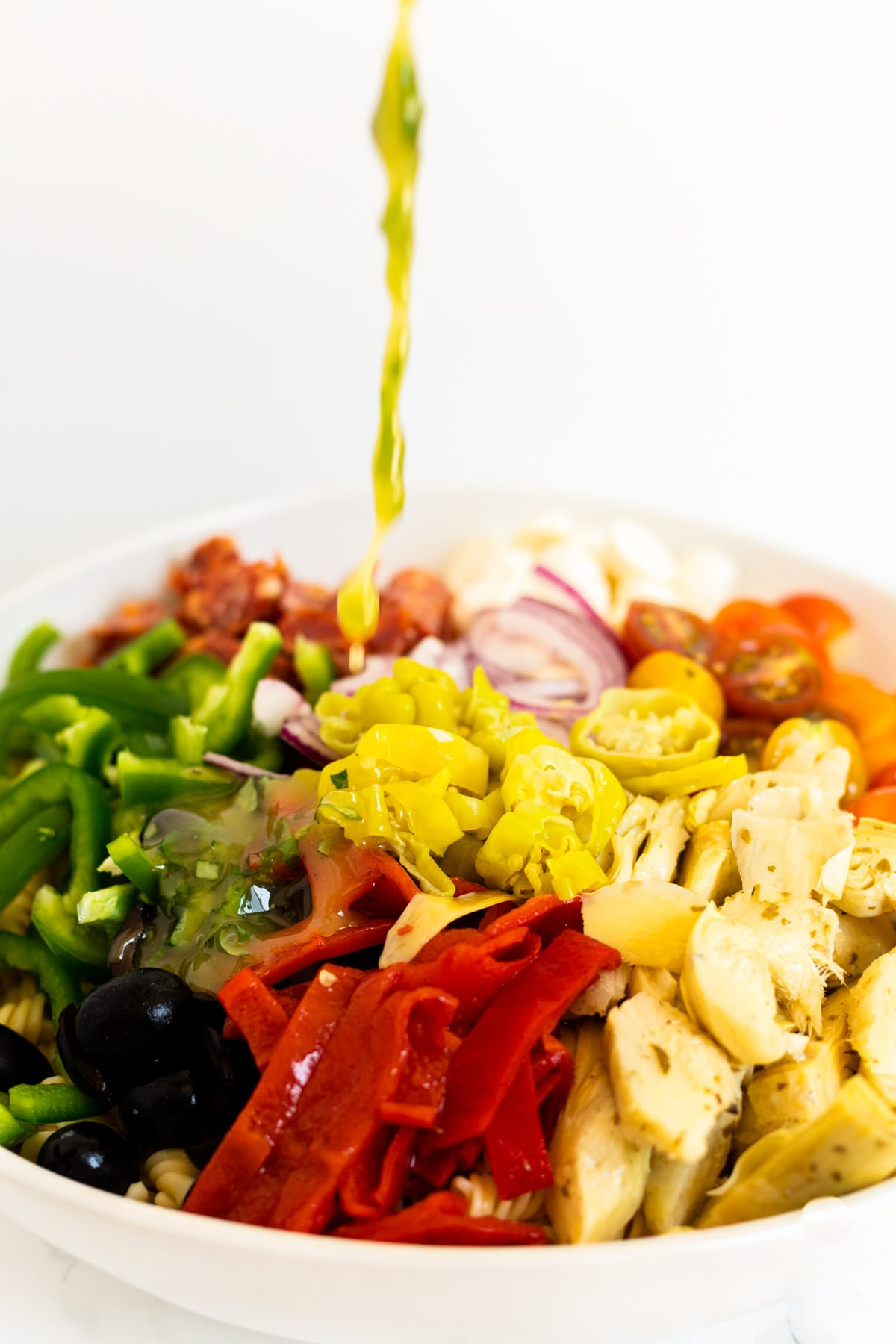 Pouring salad dressing over pasta salad.