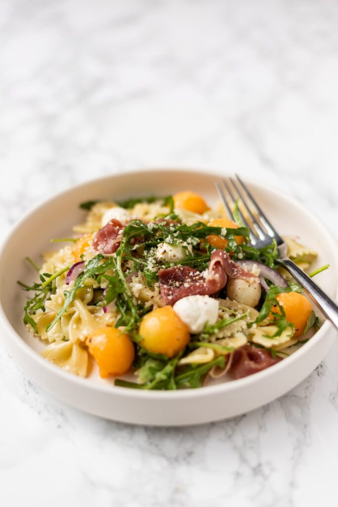 a side view of a plate of prosciutto melon pasta salad