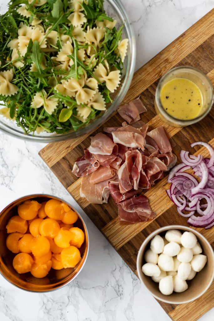 Prosciutto melon pasta salad ingredients laid out on a counter.