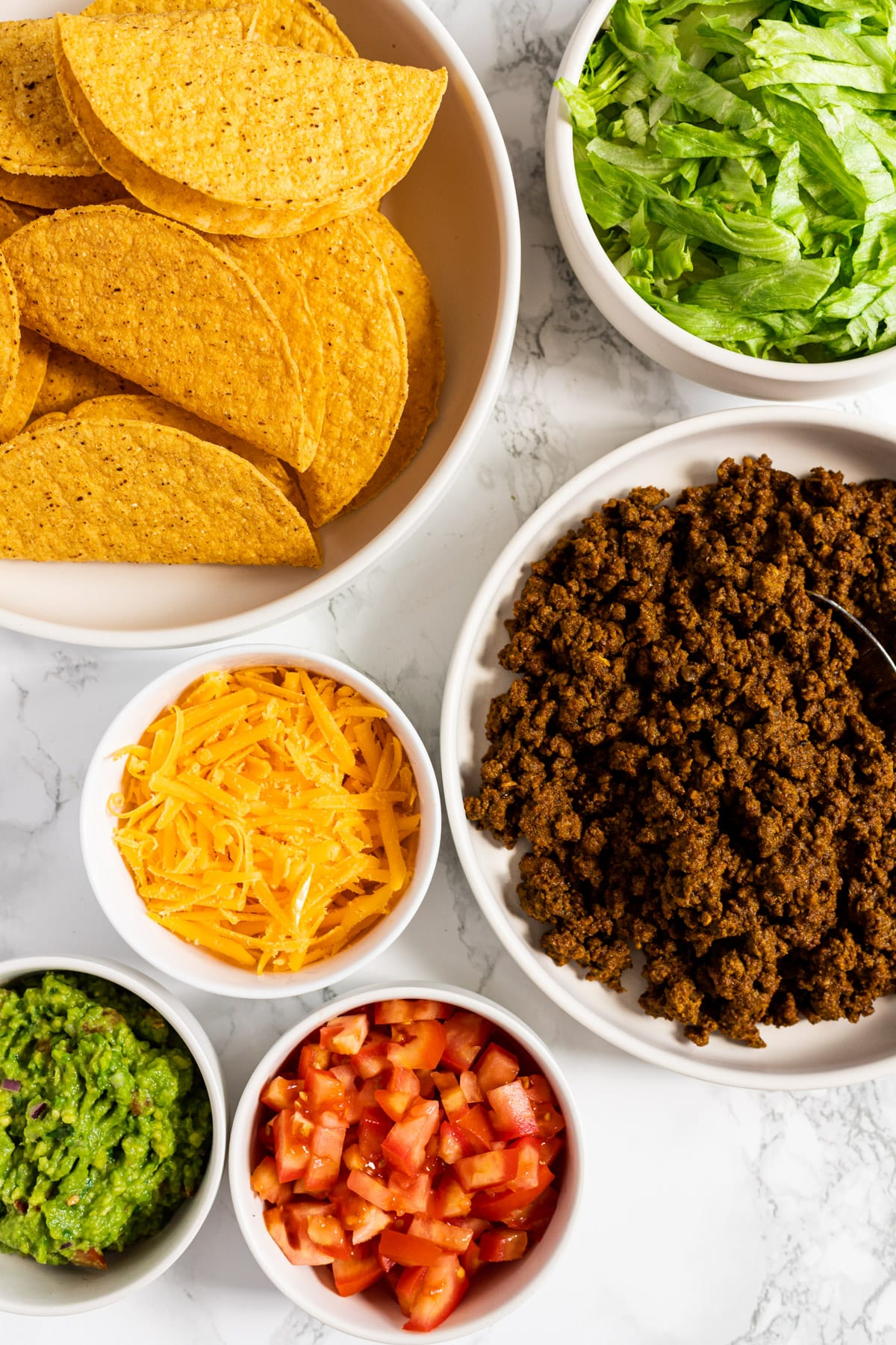 A top down view of a ground beef taco bar with all the toppings in bowls.