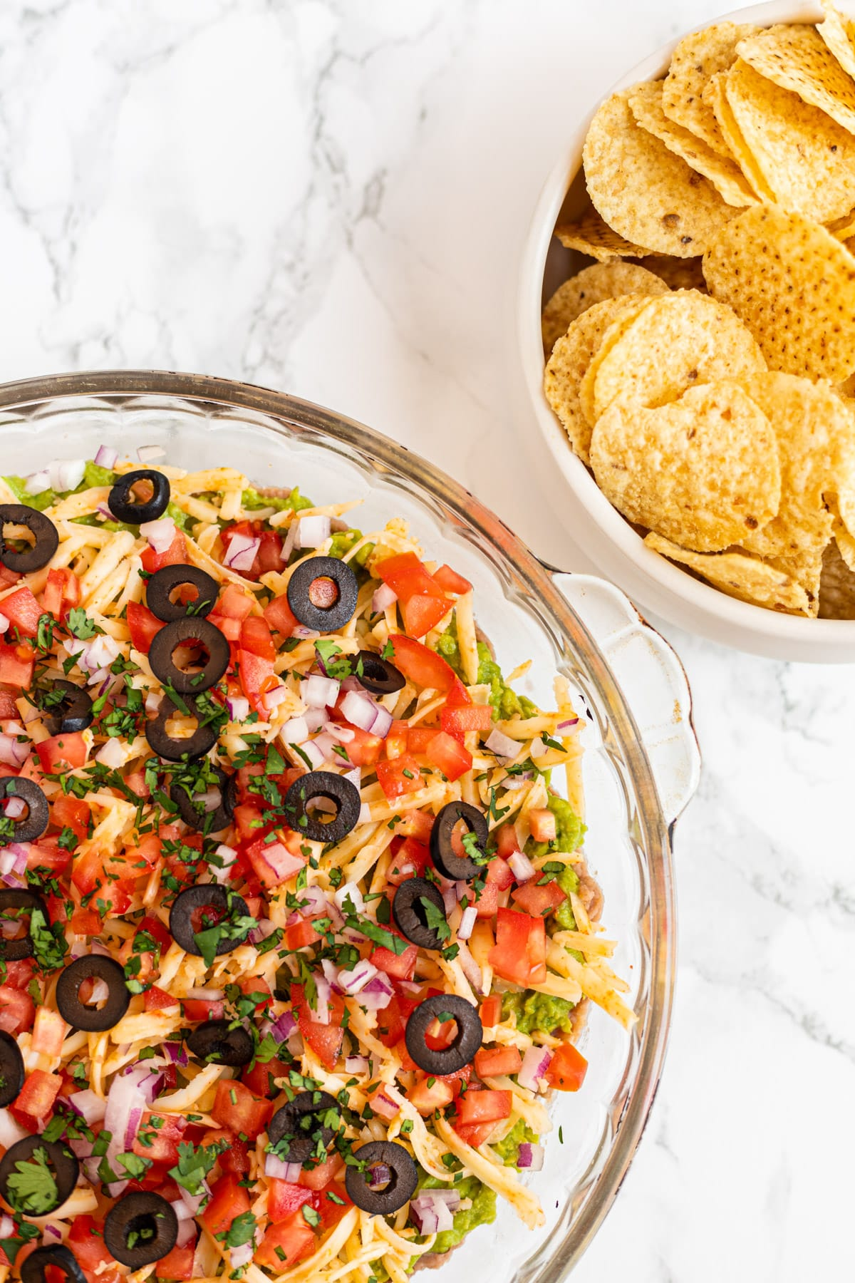 A top down view of a platter of taco dip next to aa bowl of tortilla chips.