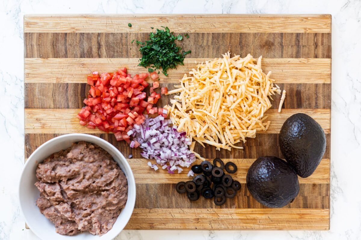 Taco dip ingredients on a cutting board with a bowl of refried beans.