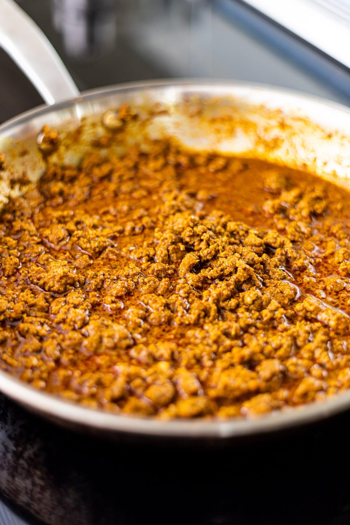 Seasoned ground beef simmering in a skillet.