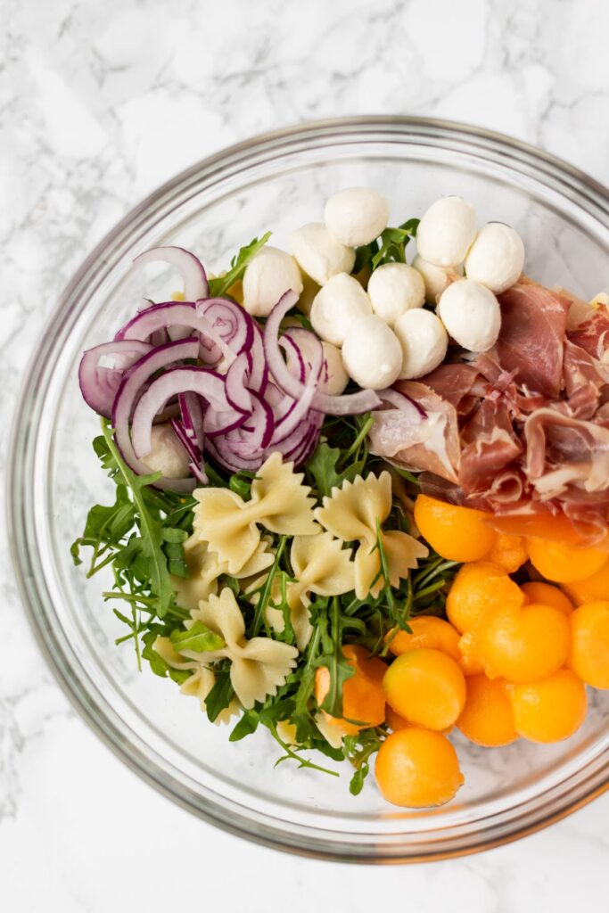 Prosciutto melon pasta salad ingredients in a glass bowl.