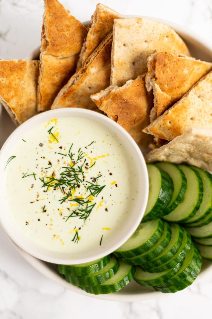 A top down view of a bowl of whipped feta dip surrounded by pita and cucumber.