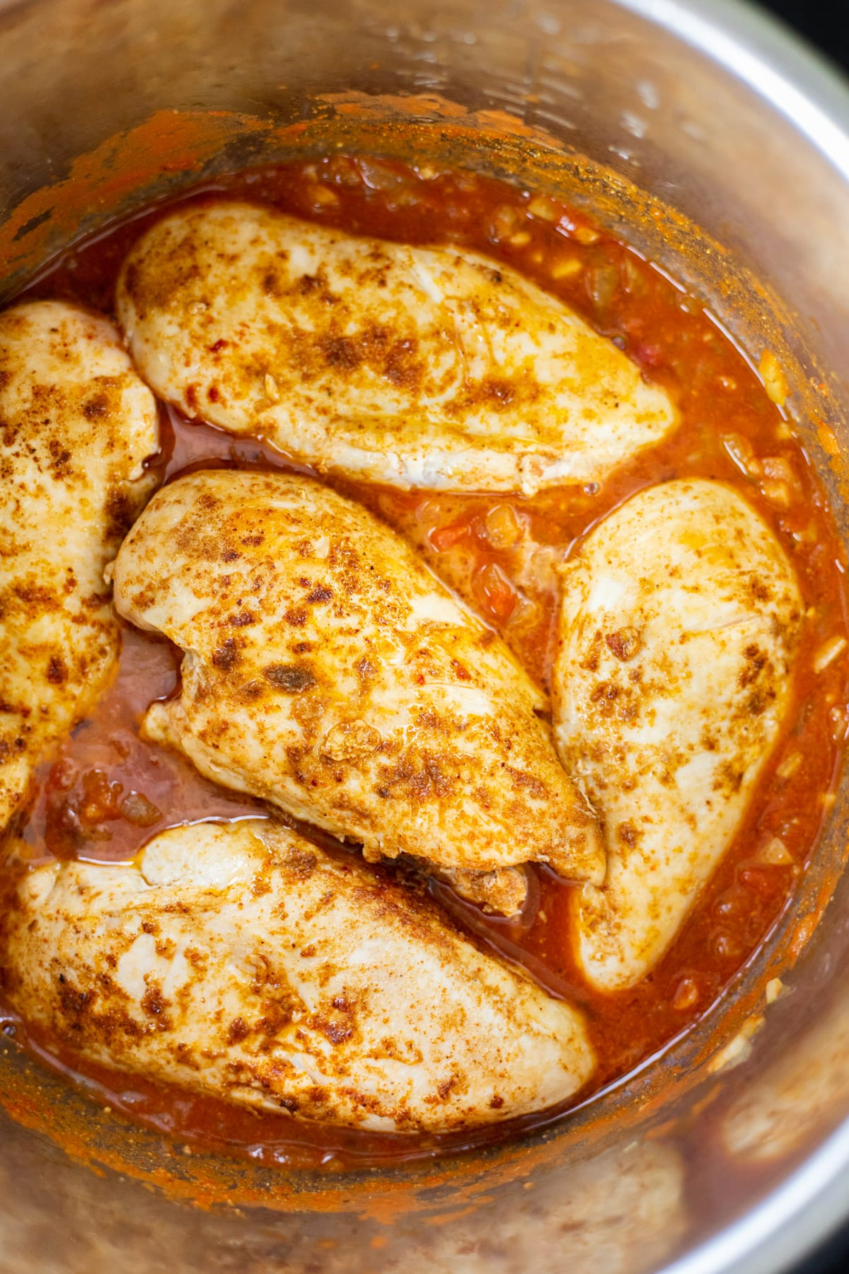 Seared chicken breasts in the Instant Pot on top of spiced tomato sauce.