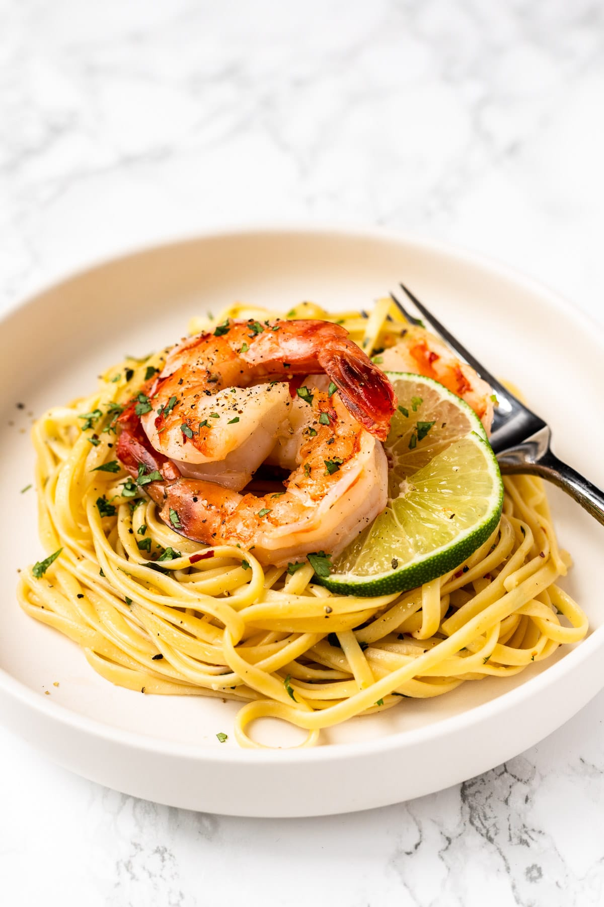 A sideview of a bowl of cilantro lime shrimp pasta.