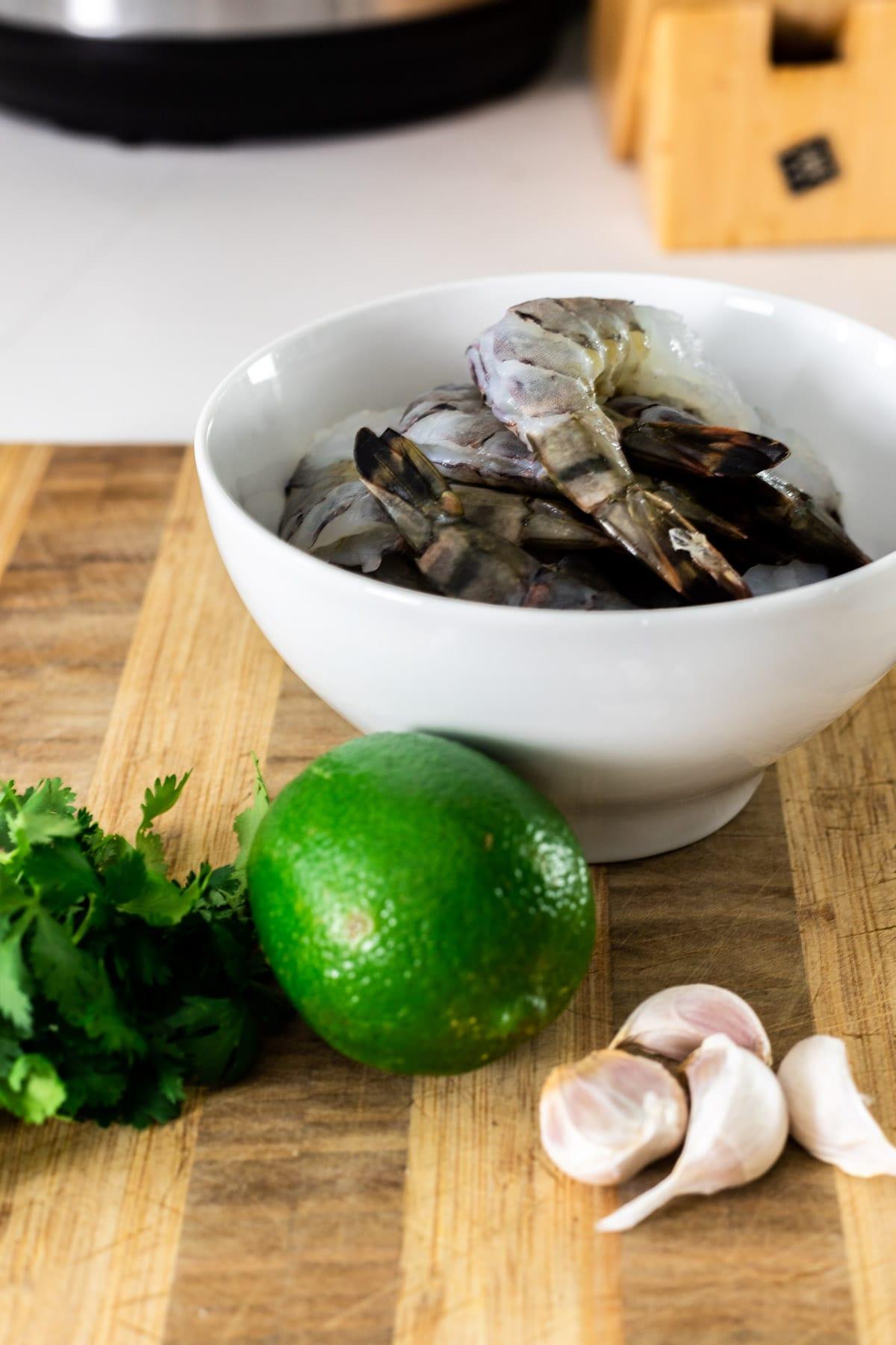 Shrimp, garlic, cilantro and lime on a cutting board.