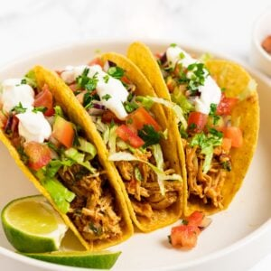 three shredded chicken tacos on a plate.