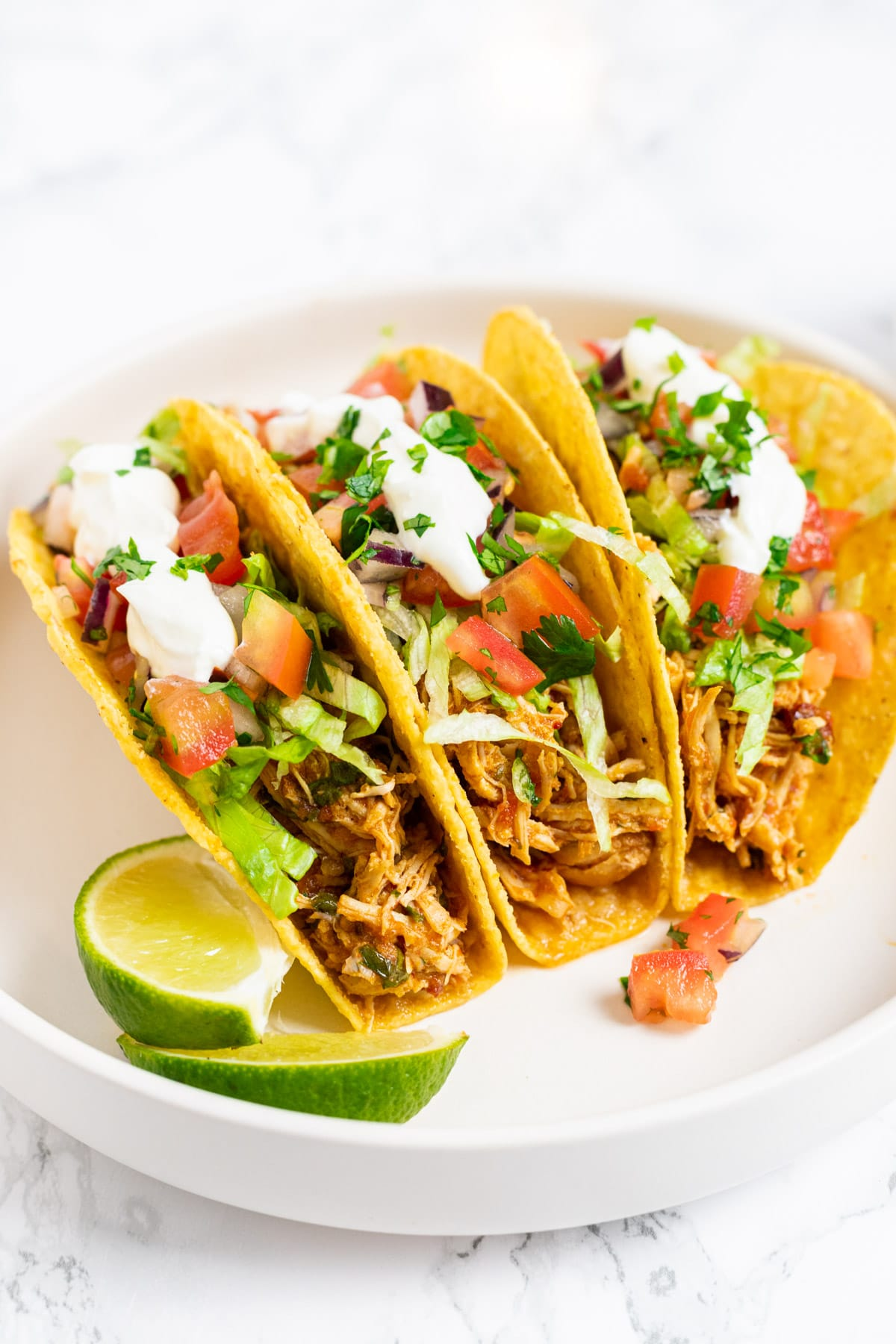 Aa side view of three shredded chicken tacos on a plate.