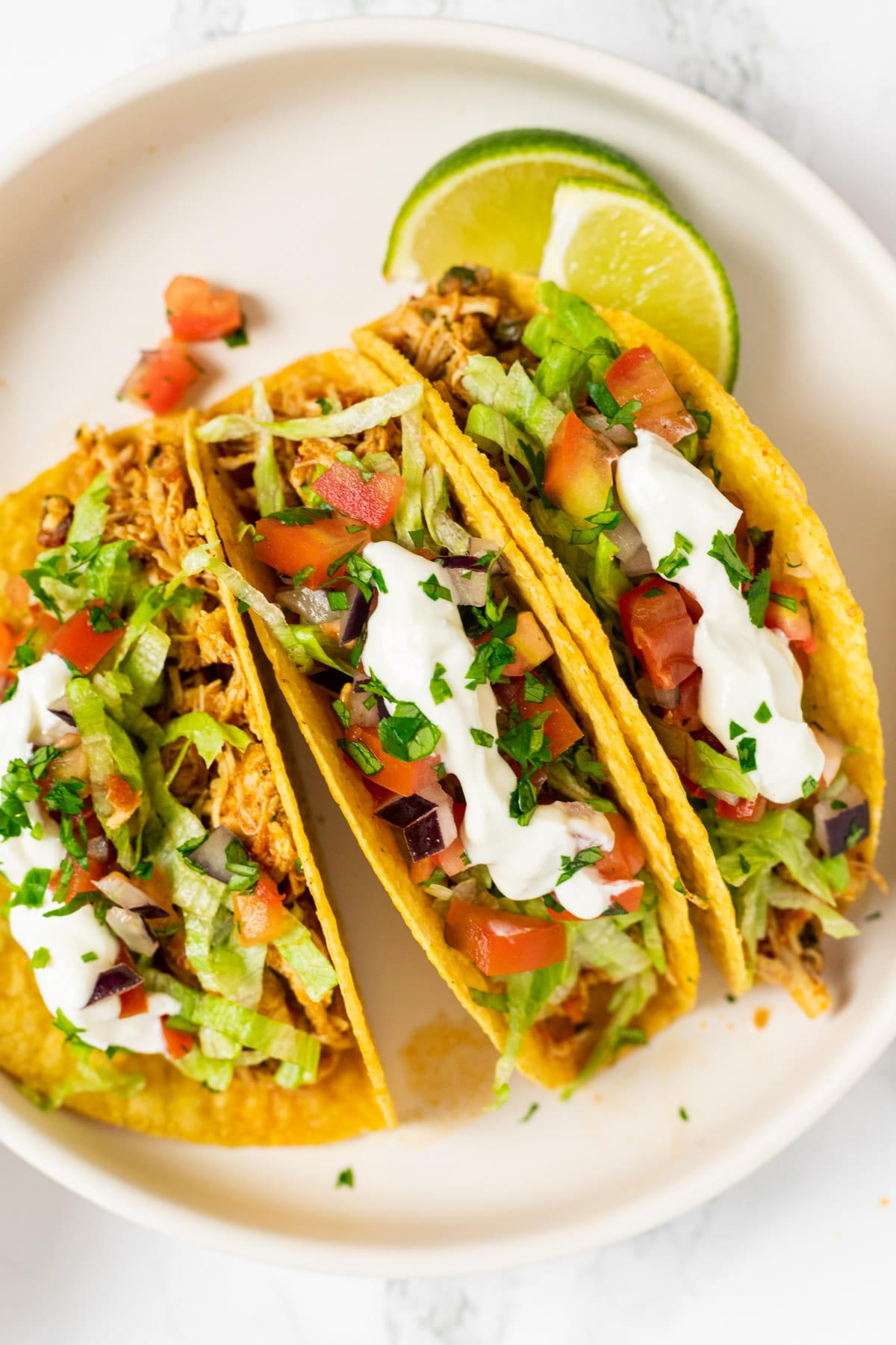 A top down view of three shredded chicken tacos on a plate.