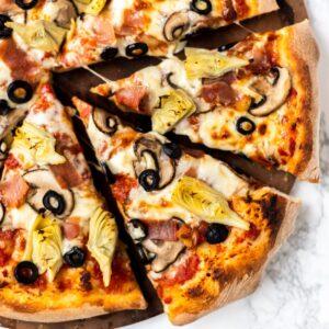 sliced pizza capricciosa on a pizza stone