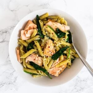 a top down view of a bowl of salmon pesto pasta
