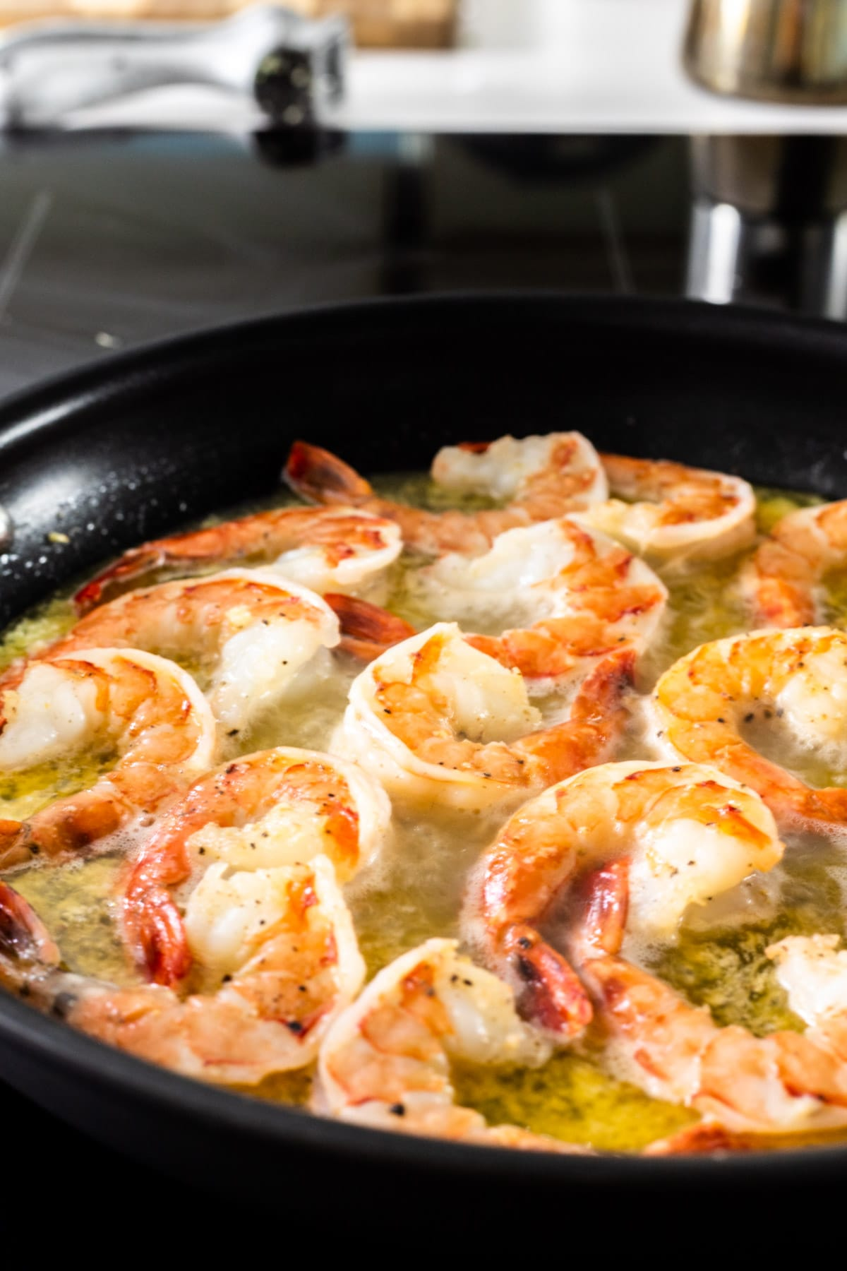 Seasoned shrimp cooking in a skillet of butter and oil.