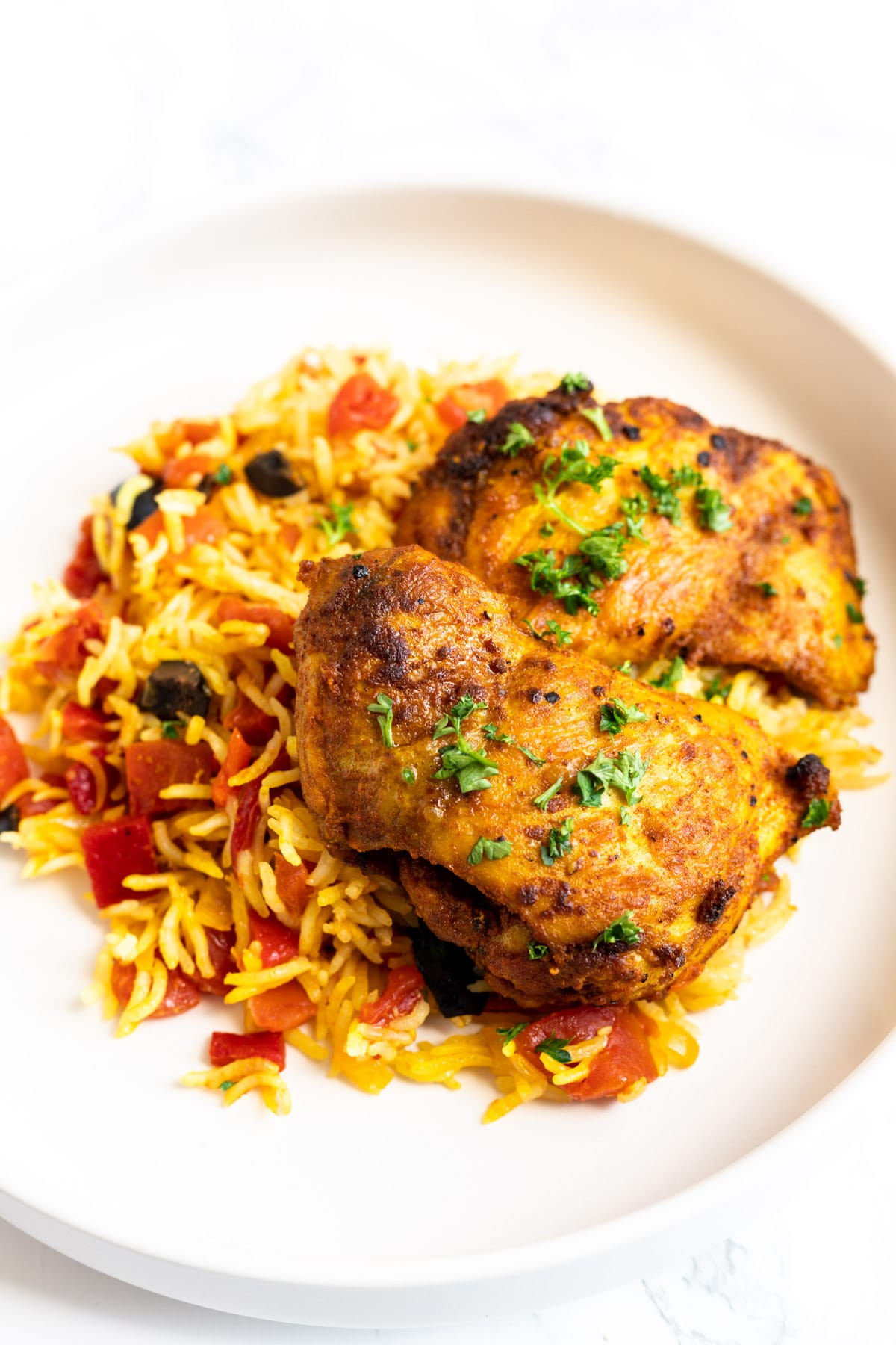 Spanish chicken and rice served on a plate.