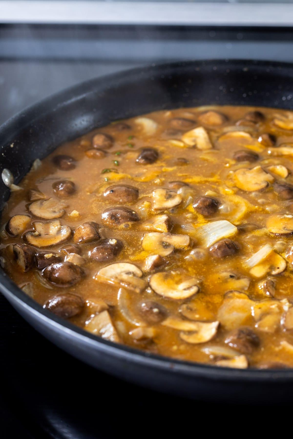 Stroganoff sauce simmering in a skilllet.