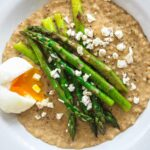 A top down view of a bowl of oatmeal with egg, asparagus and feta cheese.