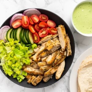 A top down view of a platter with chicken shawarma, lettuce tomato and onion next to pita bread and tahini sauce.