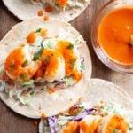 a close up view of bang bang shrimp tacos on a wooden board next to a bowl of bang bang sauce.