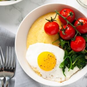A close up view of a bowl of polenta topped with a fried egg, spinach and tomatoes.