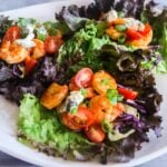 A close up view of three buffalo shrimp lettuce wraps on a plate.