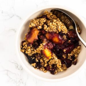 A top down view of a bowl of chai mango blueberry crisp