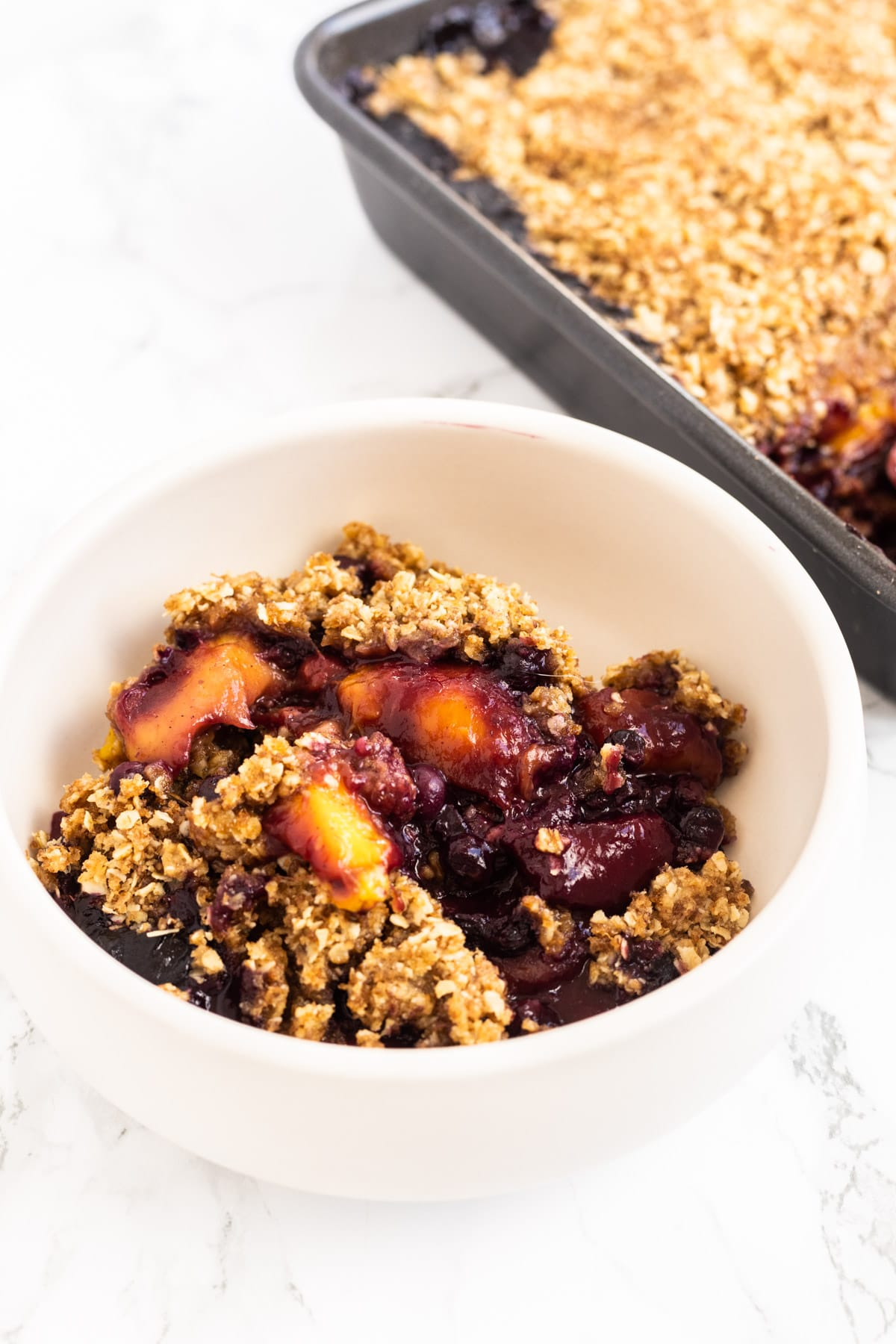 A side view of a bowl of chai mango blueberry crisp.