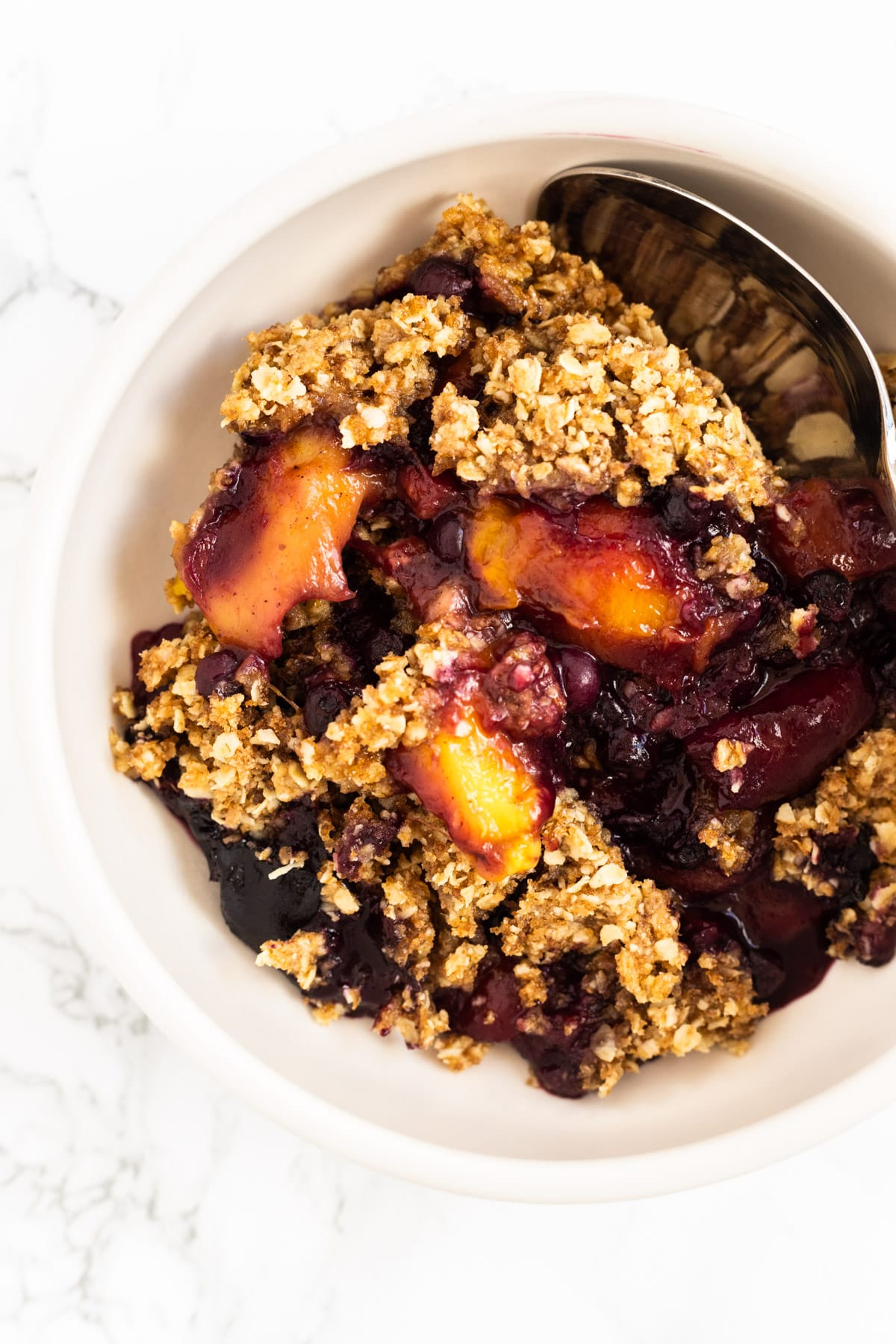 A top down view of a bowl of chai mango blueberry crisp.