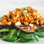 A side view of a plate with spinach topped with grilled eggplant and chickpea salad.