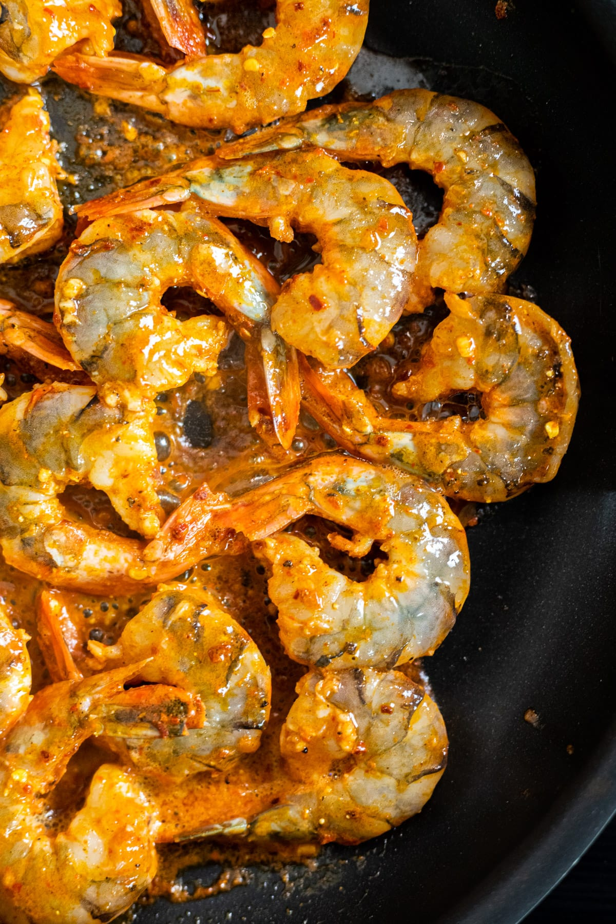 Chili seasoned shrimp cooking in a skillet.