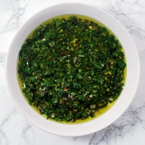 a close up view of a bowl of chimichurri sauce.