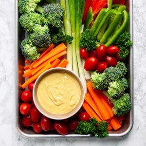 a top down view of a platter of veggies with a bowl of curry dip on it.
