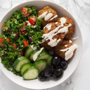 a top down view of a falafel bowl drizzled with tahini sauce.