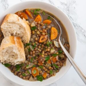 a bowl of french lentil soup with two slices of crusty bread in it.