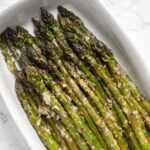 a close up view of garlic parmesan asparagus in a serving dish.