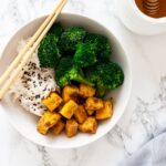 A top down view of honey garlic tofu in a bowl with broccoli and rice.