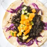 A close up view of a jerk black bean taco with mango salsa on it.