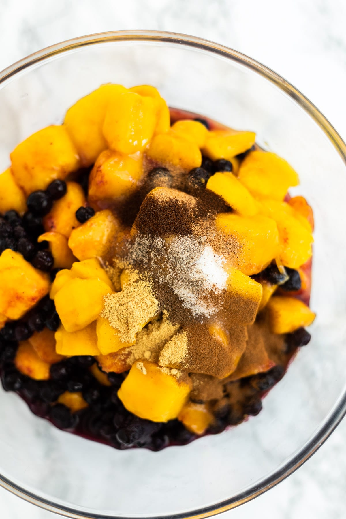 A top down view of a bowl of mangos and blueberries topped with sugar and spices.
