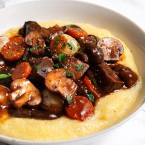 A close up of a bowl of mushroom bourguignon served over polenta.