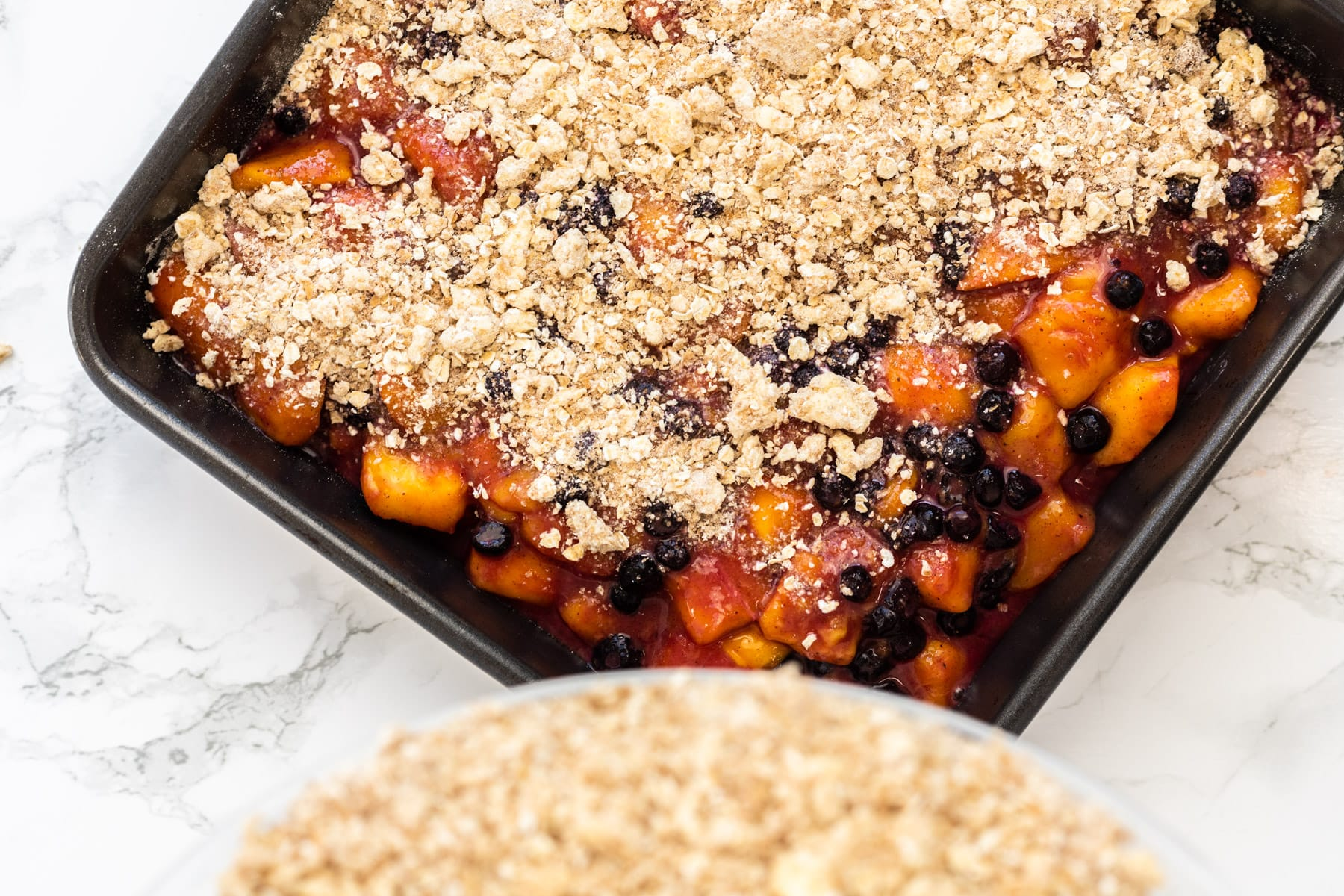 Pouring crumble topping over a baking dish filled with spiced mangoes and blueberries.