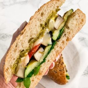 A close up view of a hand holding half a roasted vegetable sandwich.
