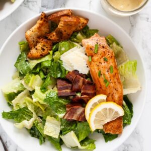 A top down view of a bowl of salmon caesar salad.