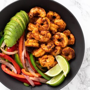 a top down view of a serving bowl with shrimp, sautéed veggies, sliced avocado and limes.
