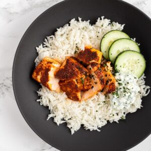 A top down view of a bowl with rice, tandorri salmon, raita and cucumber.