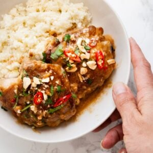a hand holding a bowl of Thai peanut chicken with cauliflower rice.