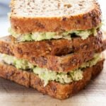 A close up view of a tuna avocado salad sandwich.